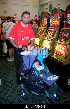 Man and baby in games arcade playing on fruit machines. - Stock Photo
