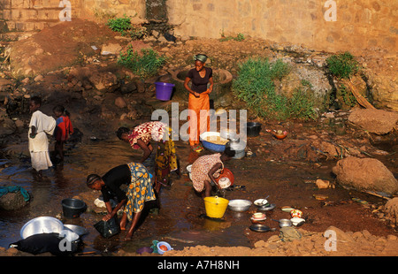 People washing clothes in the river in Kibidwe district the old part of town Bobo Dioulasso Burkina Faso - Stock Photo