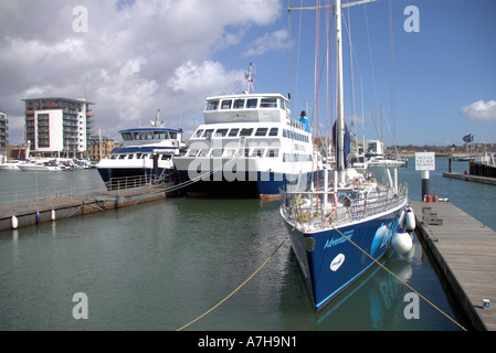 a yacht and two twin hulled passenger catamarans in the Ocean Village Marina Southampton - Stock Photo