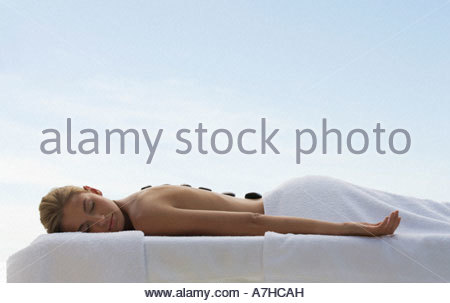 A young woman receiving a hot stone holistic treatment - Stock Photo