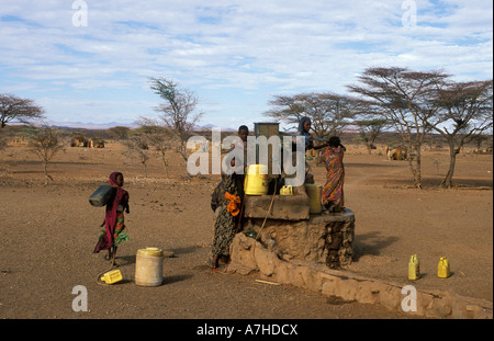 Gabbra girls collecting water from a well, Chalbi desert, Kenya - Stock Photo