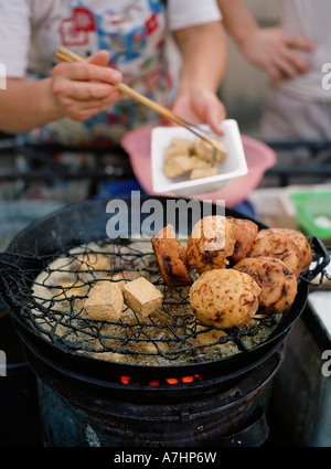 A Chinese woman prepares street food of friend tofu dofu and other delights in Shanghai - Stock Photo