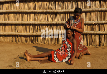 Swazi girls platting hair Mantenga village Swaziland - Stock Photo