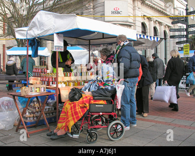 elderly disabled woman in wheelchair looking at preserves stall Farmers Market Worthing West Sussex - Stock Photo