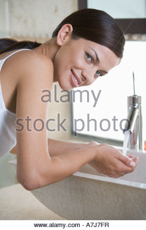 A woman washing at a sink - Stock Photo