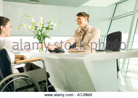 A receptionist greeting a woman in a wheelchair - Stock Photo