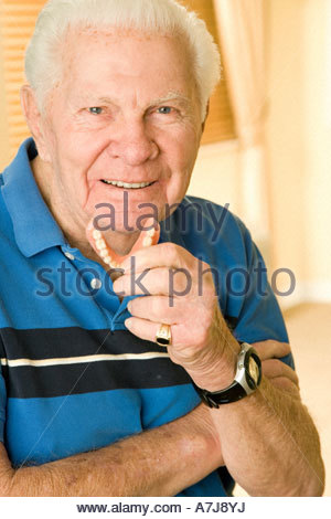 An elderly man holding his false teeth - Stock Photo