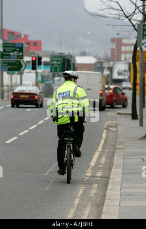 PSNI police officer on mountain bike looks to the side going down Victoria Street on St Patricks Day Belfast Northern - Stock Photo