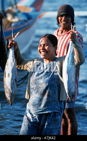 Elated expression on the face of a Balinese fisherman s wife holding a successful catch Pemuteran Bali s N coast - Stock Photo