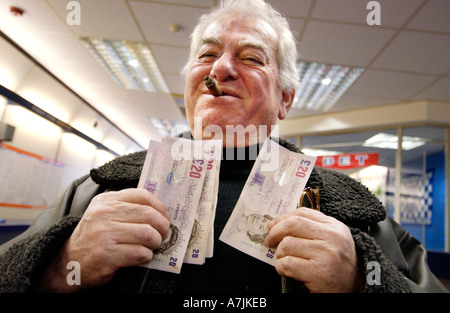 A happy punter with a big cigar waves his wad of winnings in twenty pound notes in a William Hill Betting Shop - Stock Photo