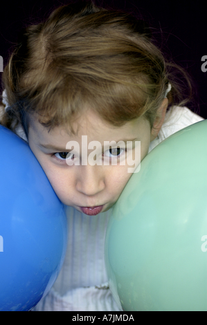 Little blond girl pausing with two balloons - Stock Photo