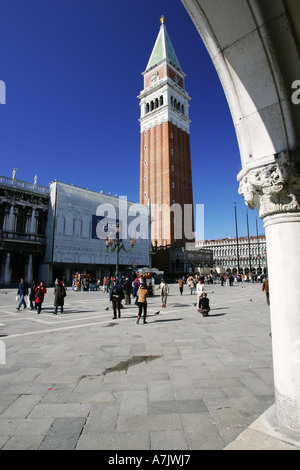 Tourists visit the popular St Marks Square landmark attraction the 99 metre tall Campanile bell tower Venice Italy - Stock Photo