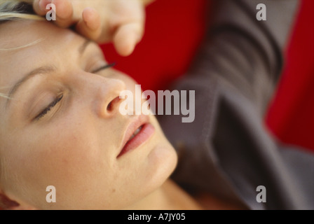 Close up of a young woman lying down with her eyes closed - Stock Photo