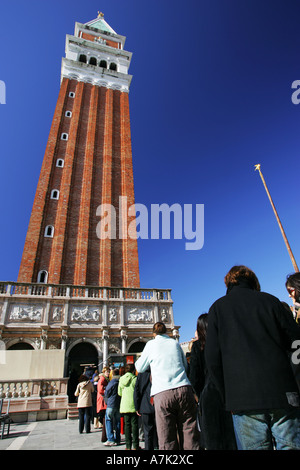 Tourists queue outside popular St Marks Square landmark attraction the 99 metre tall Campanile bell tower Venice - Stock Photo