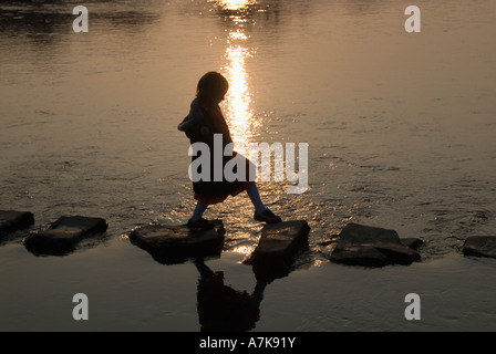 Stepping Stones - a young girl crossing a river at dusk. - Stock Photo