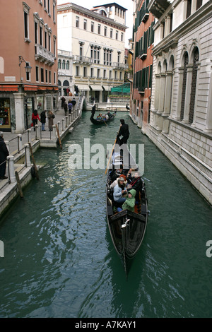 Tourists enjoy a traditional boat trip ride in a Venetian Gondola on a central Venice canal, Veneto Italy Europe - Stock Photo