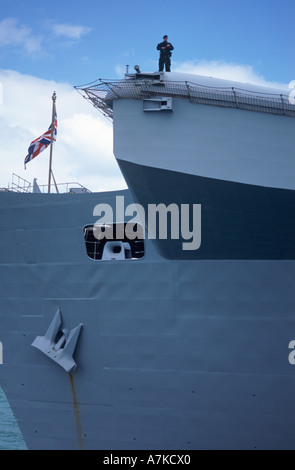Soldier standing guard on curved ramp of British aircraft carrier HMS Invincible, Portsmouth Harbour, England - Stock Photo
