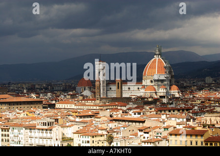 World famous landmark cathedral the Duomo in Florence Firenze is painted with sunlight as dark storm rolls over - Stock Photo