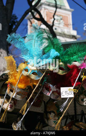 Colourful Venetian carnival masks for sale on a typical tourist souvenir stall near St Marks square central Venice - Stock Photo