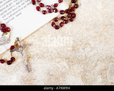 Rosary beads on a book of psalms and sandstone background with copy space - Stock Photo