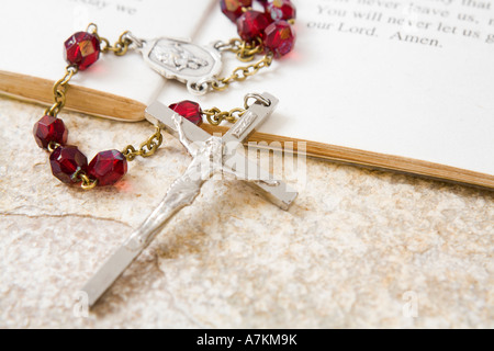 Rosary beads on a book of psalms and sandstone background - Stock Photo