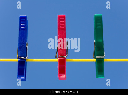 Clothes pegs on a washing line against a blue sky - Stock Photo
