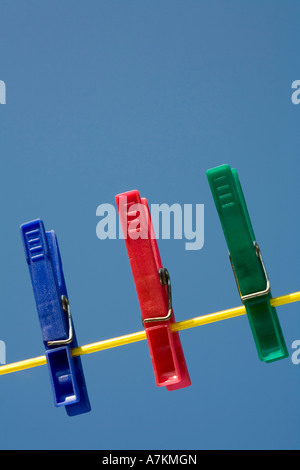 Clothes pins on a washing line against a blue sky - Stock Photo