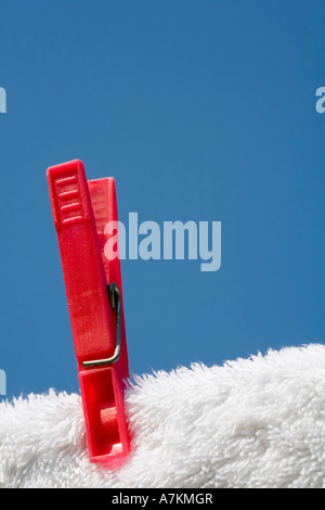 Clothes pin on a white towel and washing line against a blue sky - Stock Photo