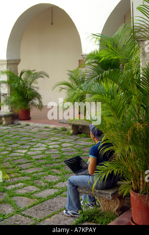 A student using their laptop in the inner courtyard of the University of Yucatan - Stock Photo