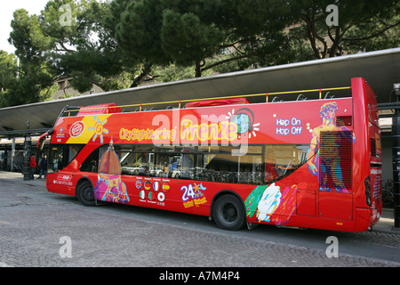 Bright red open top Florence tourist visitor sightseeing bus prepares to leave a Firenze bus stop, Tuscany Italy - Stock Photo