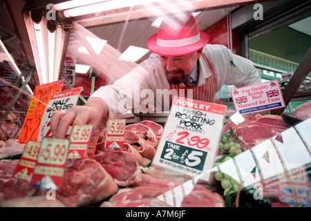 A butcher arranges his display of meat in the window of his shop in Birmingham UK - Stock Photo