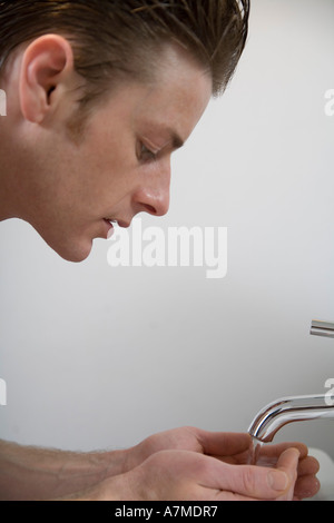 Man looking down and cupping hands under faucet - Stock Photo