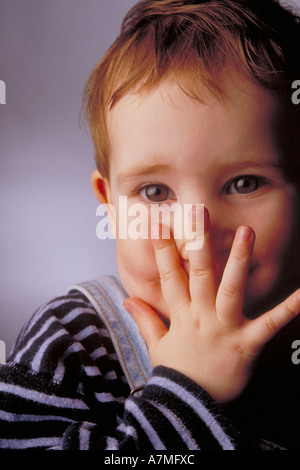 portrait of three years old boy hiding his face behind his hand - Stock Photo