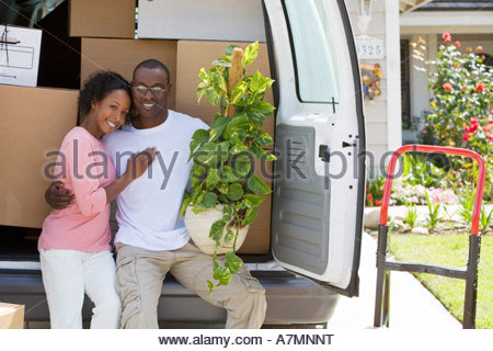 Couple moving house standing beside van in driveway man holding pot plant smiling portrait - Stock Photo