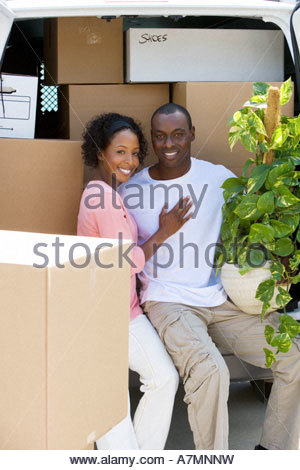 Couple moving house sitting in rear of van in driveway man holding pot plant smiling portrait - Stock Photo