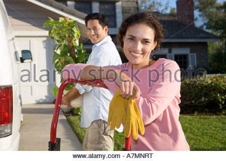 Couple moving house man beside van with pot plant woman leaning on hand dolly smiling portrait - Stock Photo