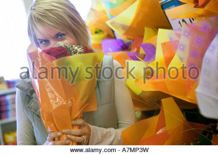 Woman smelling flower bouquet beside shop display in florists face obscured portrait - Stock Photo