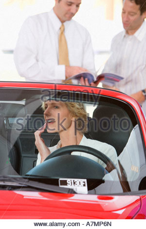 Woman sitting in red convertible in car showroom watching salesman showing man brochure in mirror - Stock Photo