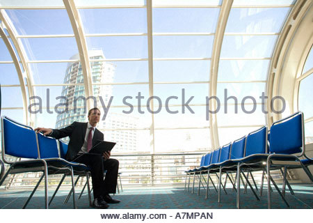 Businessman waiting in airport departure lounge using laptop side view - Stock Photo