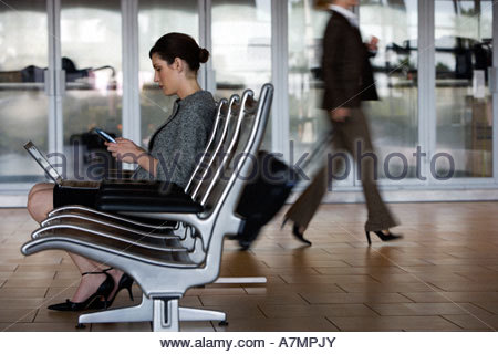 Businesswoman sitting in waiting area using laptop and electronic organiser profile - Stock Photo
