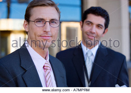 Two businessmen standing outside building smiling portrait differential focus - Stock Photo