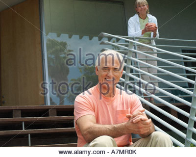 Senior couple relaxing at home woman standing on veranda man sitting on steps smiling portrait - Stock Photo