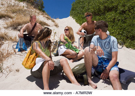 Group of teenagers 17 19 sitting on sand dune at beach talking low angle view - Stock Photo