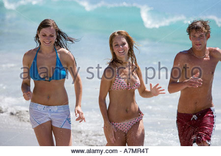 Two teenage girls and teenage boy 17 19 running along beach in surf smiling front view portrait - Stock Photo