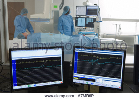 Doctors scanning patient in hospital visual monitors in foreground - Stock Photo