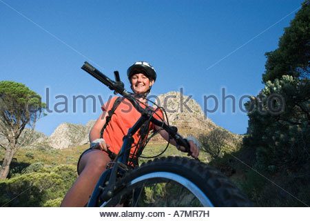 Female mountain biker sitting on bicycle in valley smiling portrait low angle view - Stock Photo