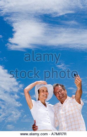 Senior couple standing on beach man taking photograph with camera phone smiling low angle view - Stock Photo