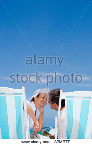Affectionate senior couple sitting in deckchairs on beach about to kiss smiling rear view - Stock Photo