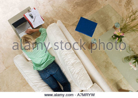 Woman lying on sofa at home using laptop resting on coffee table overhead view - Stock Photo