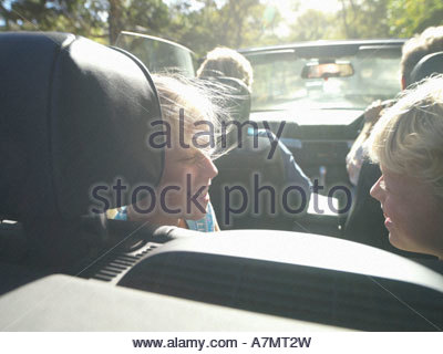 Two generation family sitting in convertible car in bright sunlight smiling rear view - Stock Photo